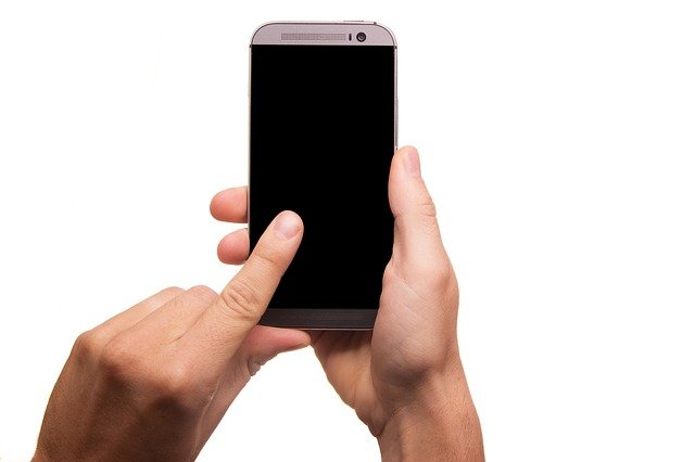 A hand holding a cell phone