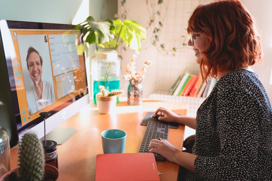 A woman standing in front of a laptop